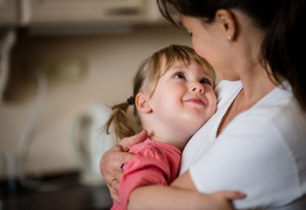 Девочка на руках у мамы. Смотрит на нее и улыбается