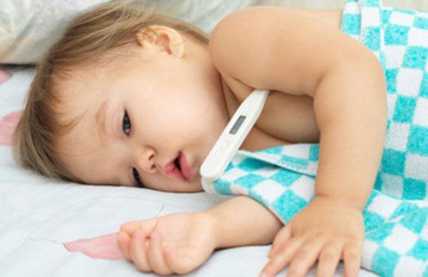 Маленький ребенок лежит, под мышкой градусник