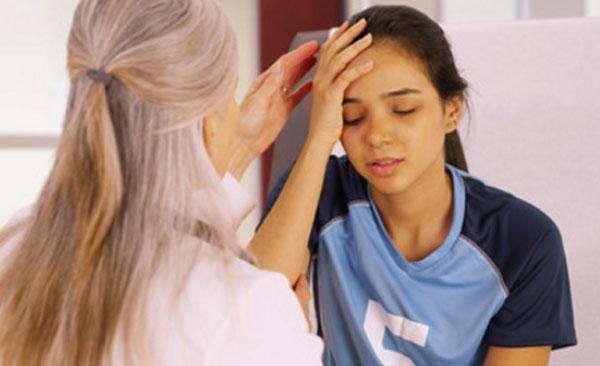 Девочка на приеме у врача держится за голову