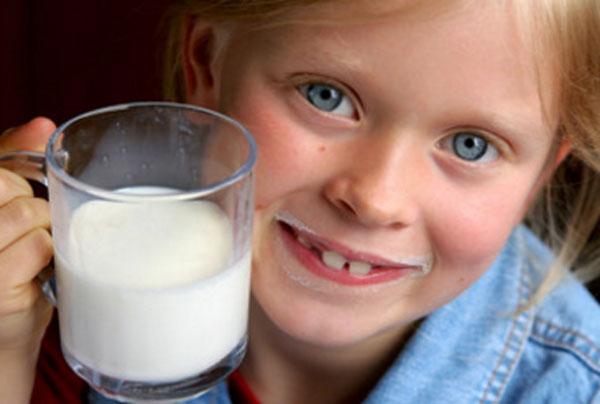 Девочка с молочными усами и чашкой молока в руках