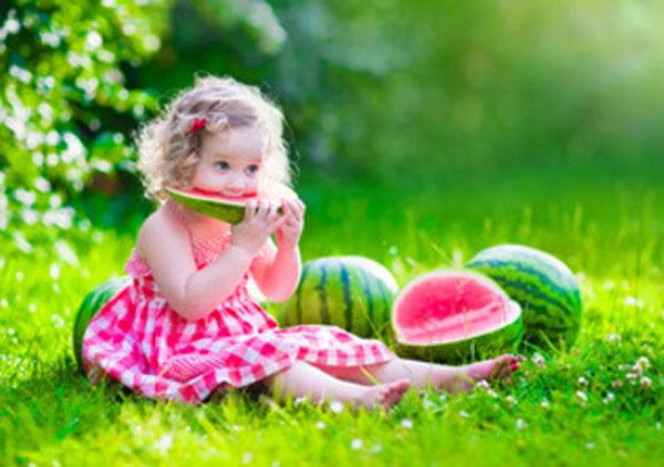 Девочка сидит на траве и ест арбуз. Рядом несколько арбузов