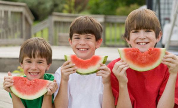 Три мальчика разных возрастов с кусочками арбуза в руках