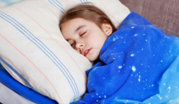 Ослабленная девочка лежит в постели с закрытыми глазами