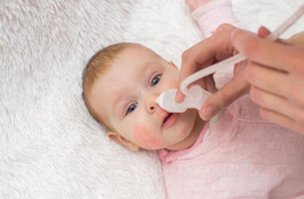Ребенку с сыпью на щеках промывают носик