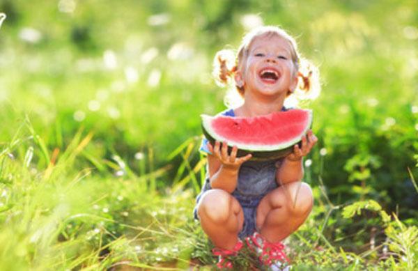Смеющаяся девочка с куском арбуза сидит в траве