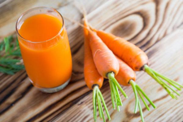 Стакан морковного сока и морковки