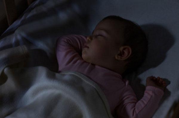Грудной ребенок спит в темной комнате