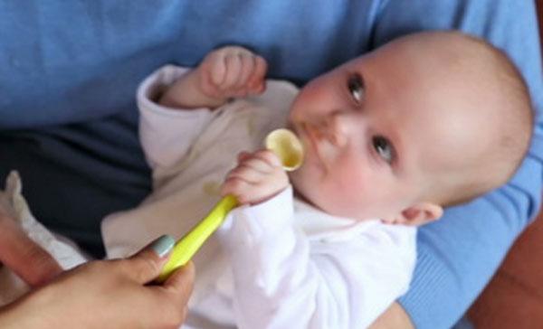Пятимесячный малыш держится за ложечку, которую ему дает мама