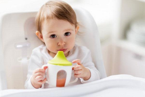 Ребенок держит в руках чашку - непроливайку, в которую налит морковный сок