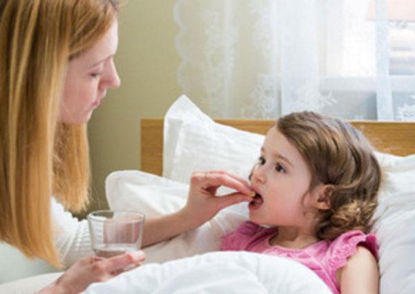 Мама дает таблетку дочери, которая лежит в постели