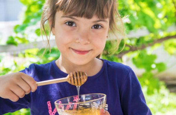 Девочка с медом в руках
