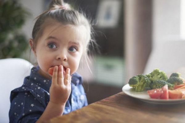 Девочка ест овощи.