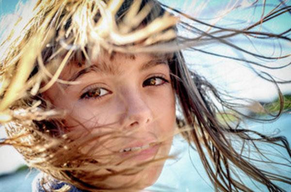 Волосы девочки разносит ветром