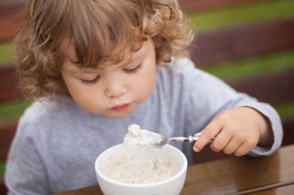Маленький ребенок ест овсяную кашу