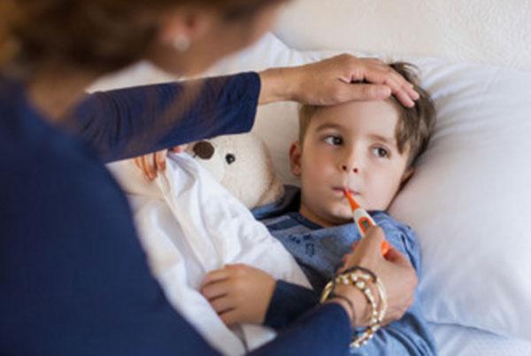 Мальчику, который лежит в постели, измеряют температуру