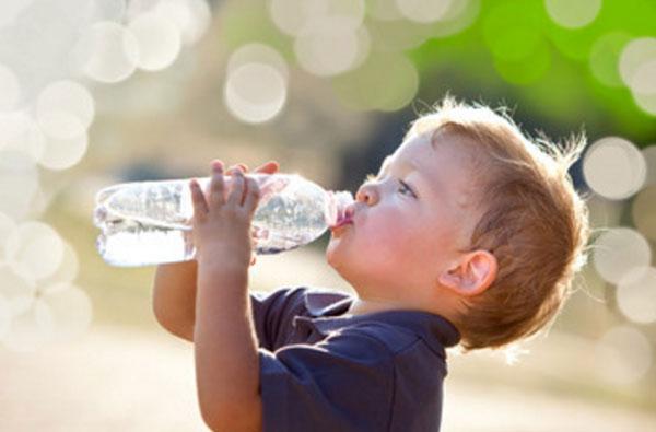 Мальчик пьет воду из бутылки