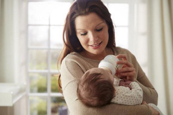 Мама держит на руках грудничка, кормит его из бутылочки