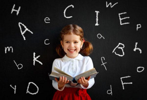 Девочка младшего школьного возраста стоит с открытой книгой в руках. Сзади нее школьная доска, на которой мелом написаны английские литеры