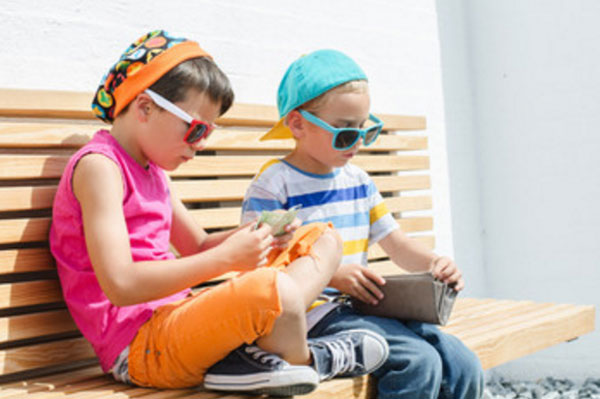 Мальчики сидят на скамейке, рассматривают, что есть в кошельке