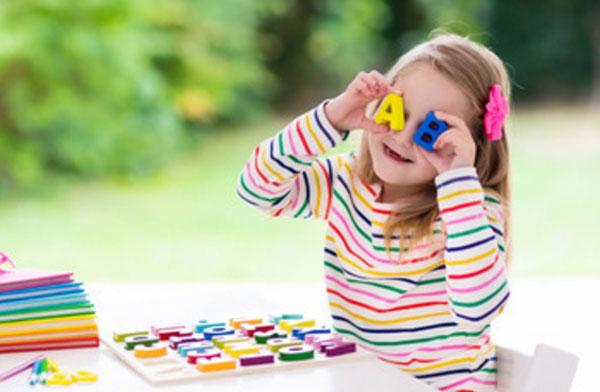 Девочка играет с английскими магнитными литерами, приставляет их к своим глазам. На столе лежит планшетка, на которой остальные литеры