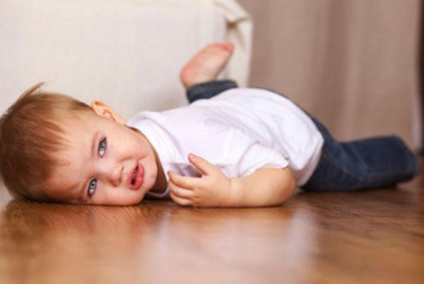 Обиженный ребенок лежит на полу. На глазах слезки