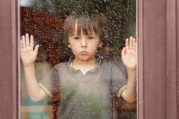 Грустный мальчик стоит у окна, за которым идет дождь