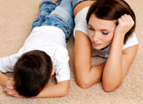 Мама лежит на полу рядом со своим сыном, который прячет лицо
