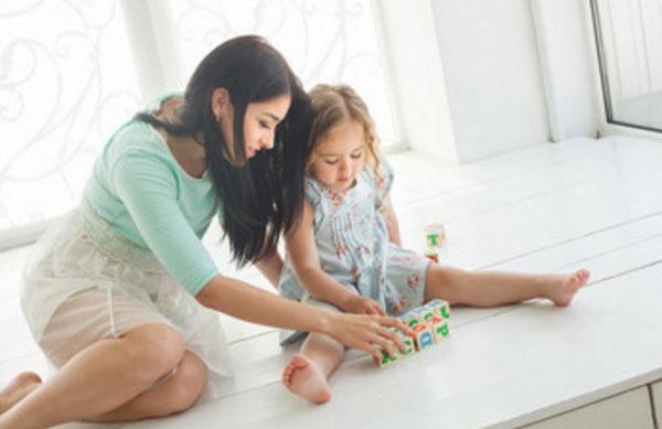 Мама с дочкой сидят на полу и собирают слова на английском при помощи кубиков, на которых изображены английские литеры