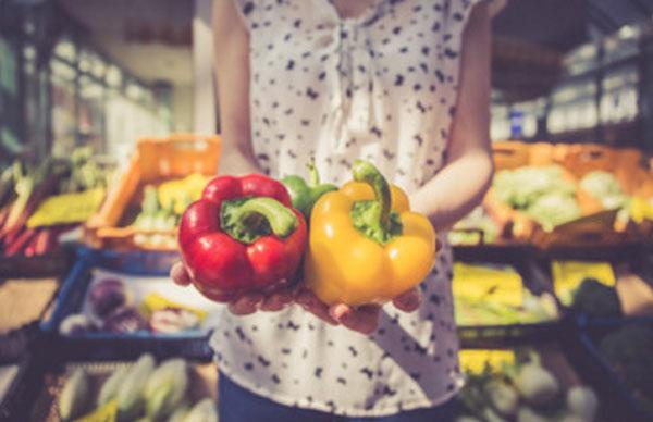 Женщина в магазине держит две перчинки