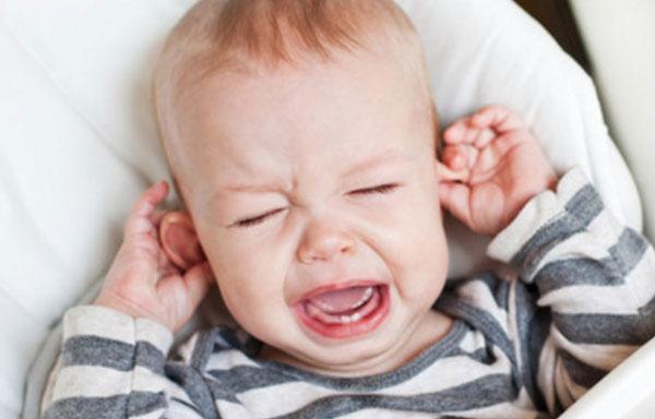 Ребенок держится за уши и плачет