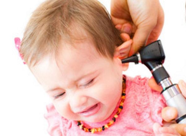 Доктор осматривает ухо маленькой девочки
