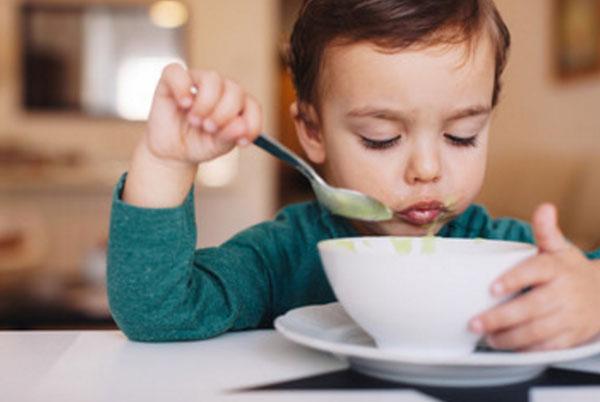 Маленький мальчик ест овощной суп