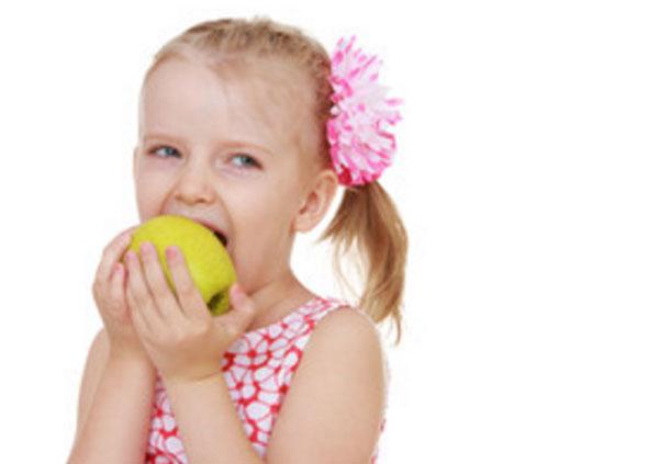 Девочка кусает желто-зеленое яблоко