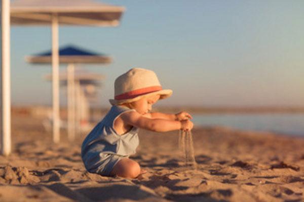 Маленький ребенок играет с песком на морском берегу