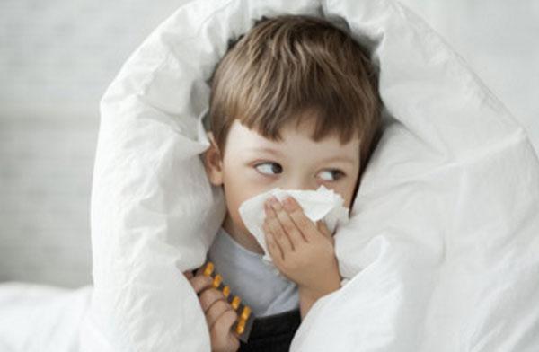 Мальчик сидит, укутавшись теплым одеялом, высмаркивается в салфетку, в руке держит таблетки
