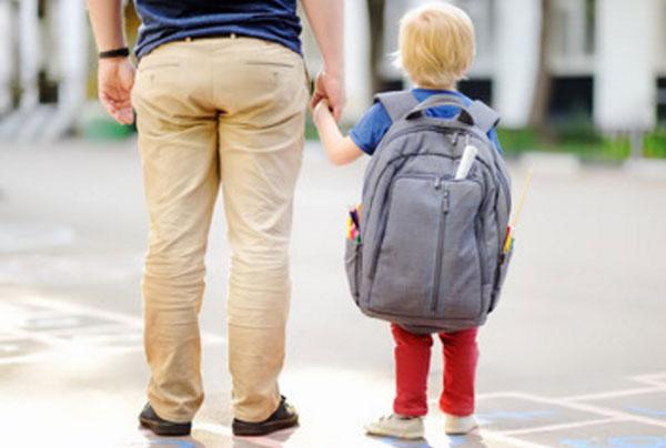 Мальчик держит папу за руку. На спине у него очень большой рюкзак