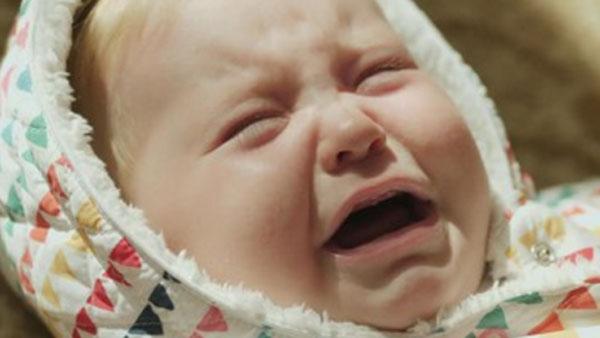 Плачущий грудничок в комбинезоне