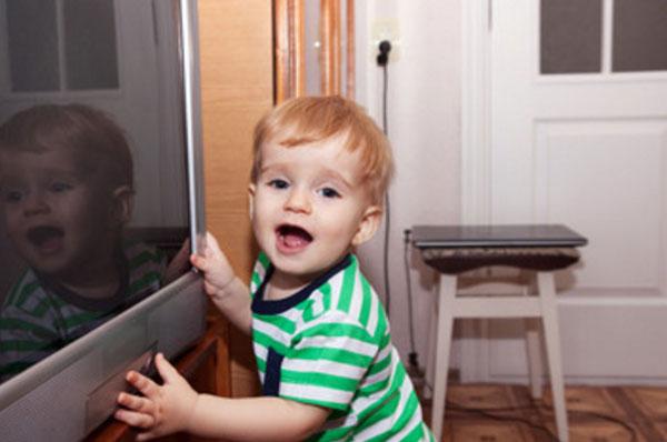 Мальчик стоит возле выключенного телевизора, пытается его включить