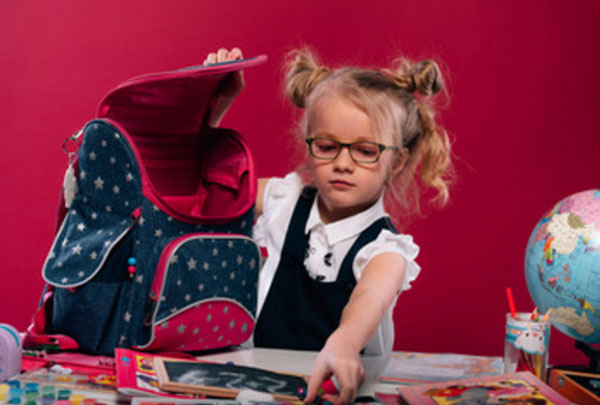 Маленькая девочка в очках собирает портфель