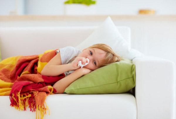 Мальчик лежит в постели, держит салфетку возле носика