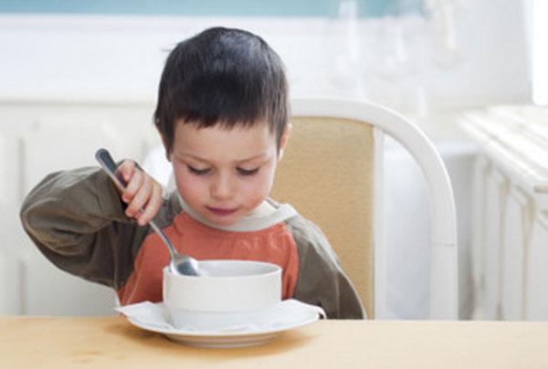 Малыш с недовольным видом водит ложкой по тарелке