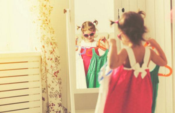 Маленькая девочка в солнцезащитных очках стоит перед зеркалом, держа в руках вешалки с платьями