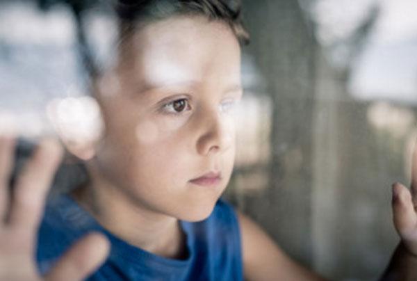 Мальчик с грустным лицом стоит у окна