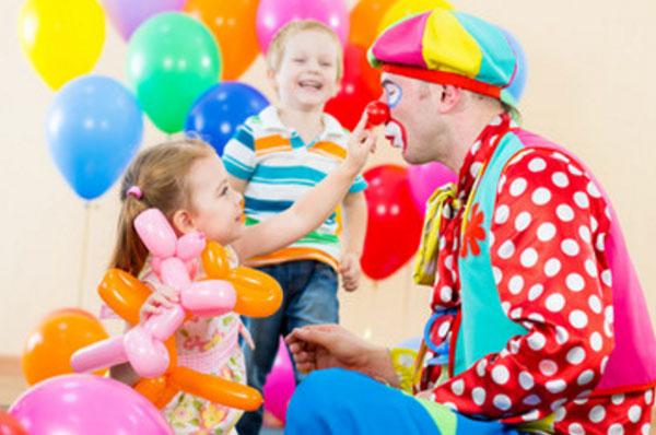 Клоун сидит возле девочки, которая пробует потрогать его нос. На заднем плане счастливый мальчик и воздушные шары