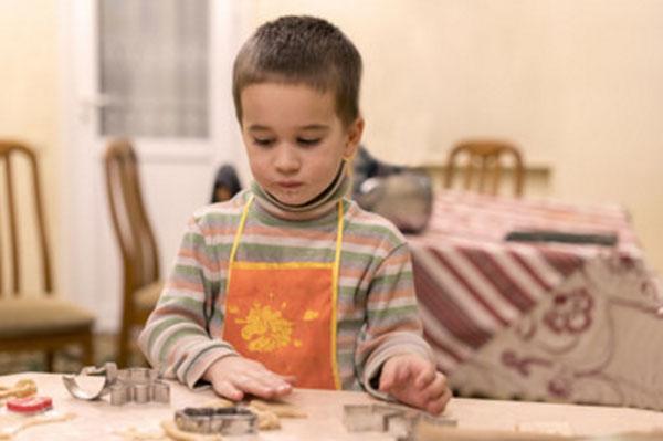 Мальчик в фартуке стоит у стола, на котором лежат его изделия