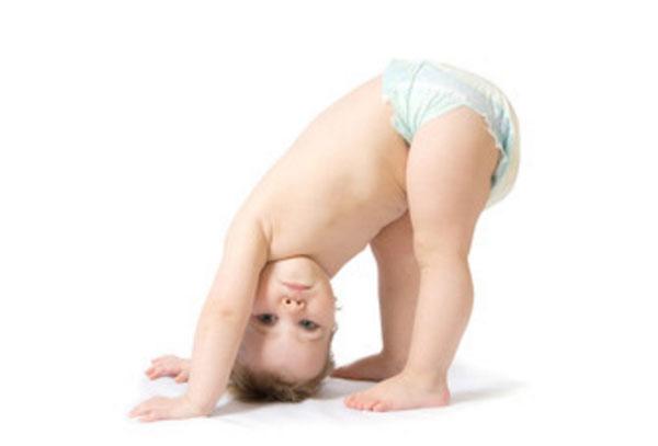 Ребенок в одном памперсе наклонился вниз головой