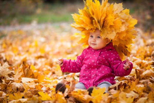 Ребенок сидит в осенней листве. На голове венок из осенних листьев