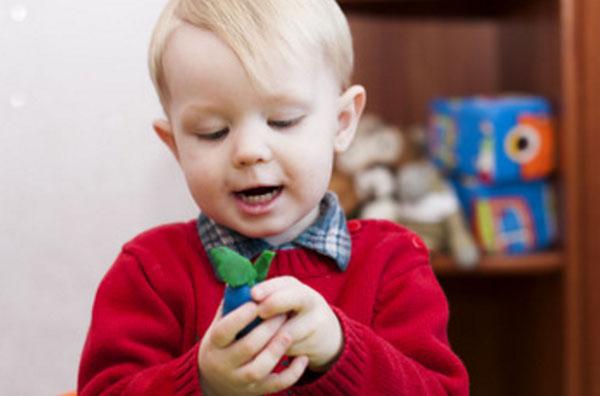 Мальчик с открытым ртом смотрит на слепленную сливу, которую держит в руке