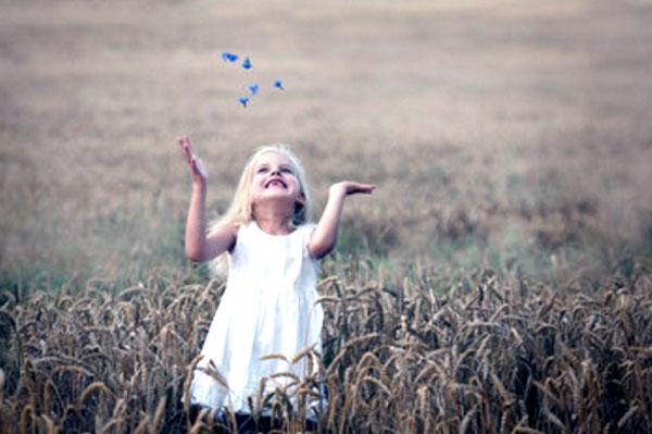 Девочка стоит посреди поля с колосьями
