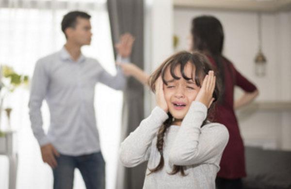 На переднем плане девочка плачет, закрывая уши. На заднем ругаются ее родители